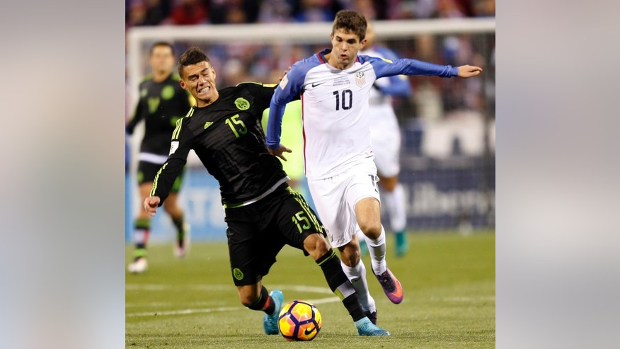 Mexico's Hector Moreno, left, and United States' Christian Pulisic chase a loose ball during the first half of a World Cup qualifying soccer match Friday, Nov. 11, 2016, in Columbus, Ohio. (AP Photo/Jay LaPrete)