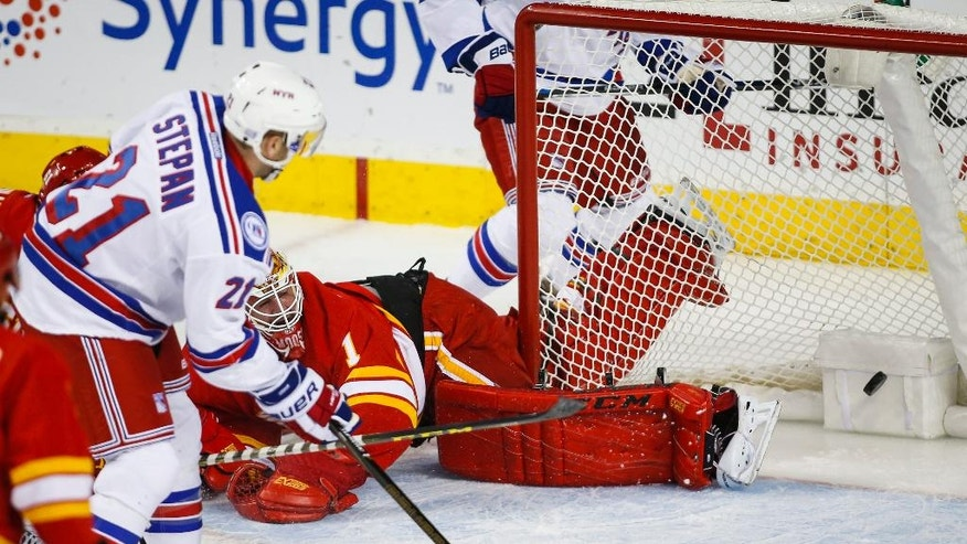 New York Rangers' Derek Stepan, left, scores on Calgary Flames goalie Brian Elliott during the first period of an NHL hockey game Saturday, Nov. 12, 2016, in Calgary, Alberta. (Jeff McIntosh/The Canadian Press via AP)