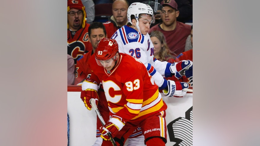 New York Rangers' Jimmy Vesey, right, is checked by Calgary Flames' Sam Bennett during the first period of an NHL hockey game Saturday, Nov. 12, 2016, in Calgary, Alberta. (Jeff McIntosh/The Canadian Press via AP)