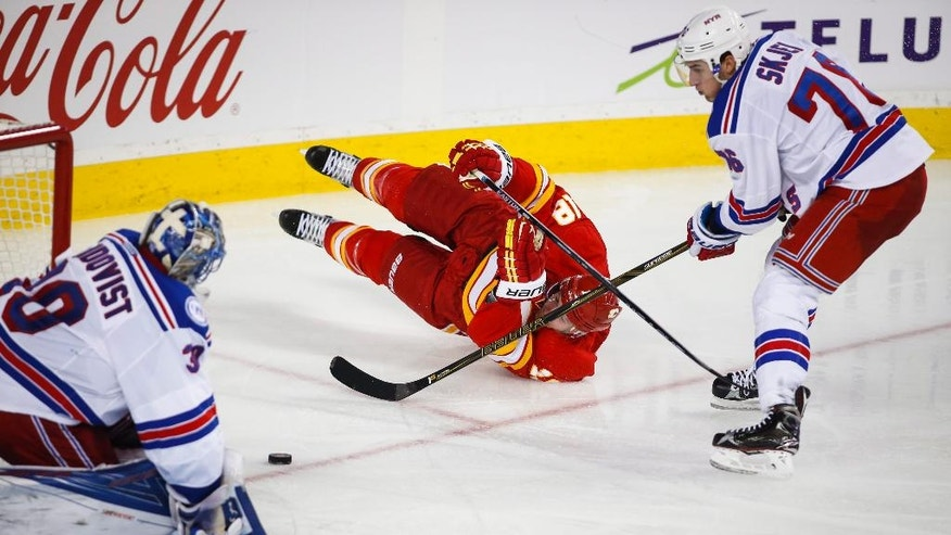 New York Rangers' Brady Skjei, right, brings down Calgary Flames' Matt Stajan in front of goalie Henrik Lundqvist, from Sweden, during the third period of an NHL hockey game Saturday, Nov. 12, 2016, in Calgary, Alberta. (Jeff McIntosh/The Canadian Press via AP)