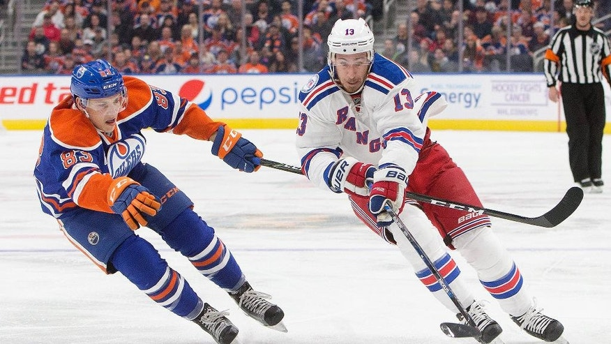 New York Rangers' Kevin Hayes (13) and Edmonton Oilers' Matthew Benning (83) battle for the puck during the first period of an NHL hockey game in Edmonton, Alberta, Sunday, Nov. 13, 2016. (Jason Franson/The Canadian Press via AP)