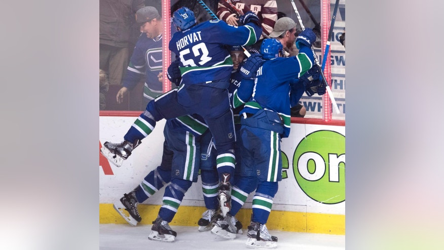 Vancouver Canucks defenseman Troy Stecher (51) celebrates his goal against the Dallas Stars with teammates Bo Horvat (53) Alexandre Burrows (14) and Sven Baertschi (47) during third period NHL hockey action in Vancouver, British Columbia, Sunday, Nov. 13, 2016. (Jonathan Hayward/The Canadian Press via AP)