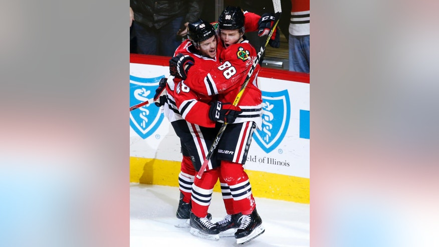 Chicago Blackhawks right wing Patrick Kane, right, celebrates with left wing Vinnie Hinostroza after scoring his goal during the second period of an NHL hockey game against the Montreal Canadiens in Chicago, Sunday, Nov. 13, 2016. (AP Photo/Nam Y. Huh)