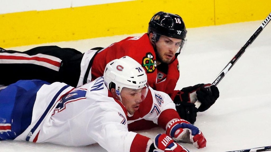 Montreal Canadiens defenseman Alexei Emelin, left, controls the puck against Chicago Blackhawks center Marcus Kruger during the second period of an NHL hockey game in Chicago, Sunday, Nov. 13, 2016. (AP Photo/Nam Y. Huh)