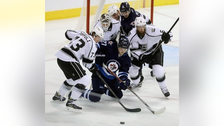Los Angeles Kings' Tyler Toffoli (73) and Jake Muzzin (6) battle with Winnipeg Jets' Nikolaj Ehlers (27) during the third period of an NHL hockey game in Winnipeg, Manitoba, Sunday, Nov. 13, 2016. (Trevor Hagan/The Canadian Press via AP)
