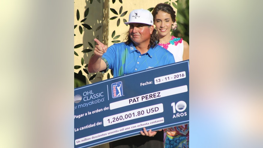 Pat Perez of the United States holds the winners check after he won the OHL Classic at Mayakoba golf tournament in Playa del Carmen, Mexico, Sunday, Nov. 13, 2016. (AP Photo/Israel Leal)