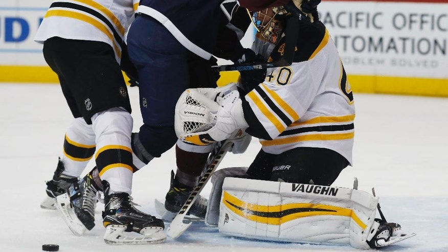 Colorado Avalanche left wing AJ Greer, center, is pushed by Boston Bruins defenseman Adam McQuaid after goalie Tuukka Rask, of Finland, stops Grer's shot in the first period of an NHL hockey game Sunday, Nov. 13, 2016, in Denver. (AP Photo/David Zalubowski)