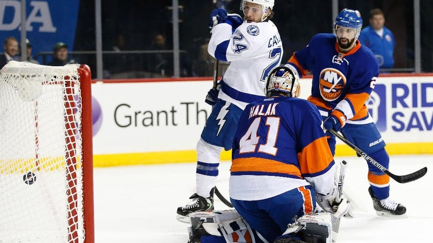 Tampa Bay Lightning right wing Ryan Callahan (24) looks over his shoulder as the puck ricochets in the net after he scored on New York Islanders' goalie Jaroslav Halak (41) of Slovakia, with Islanders' defenseman Nick Leddy (2) defending during the first period of an NHL hockey game Monday, Nov. 14, 2016, in New York. (AP Photo/Kathy Willens)