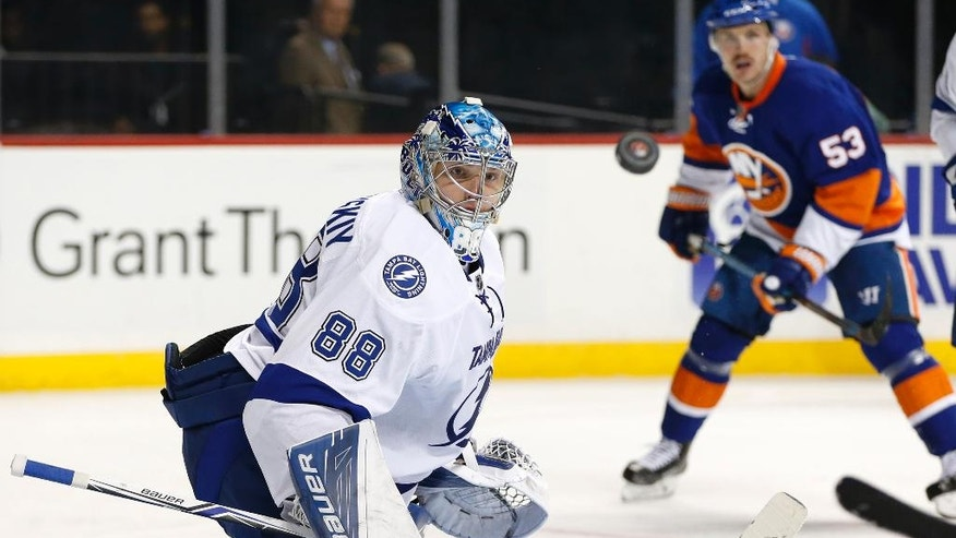 New York Islanders' center Casey Cizikas (53) watches as Tampa Bay Lightning goalie Andrei Vasilevskiy (88) of Russia keeps his eye on the puck as it sails past him after he made a save on goal during the second period of an NHL hockey game, Monday, Nov. 14, 2016, in New York. (AP Photo/Kathy Willens)