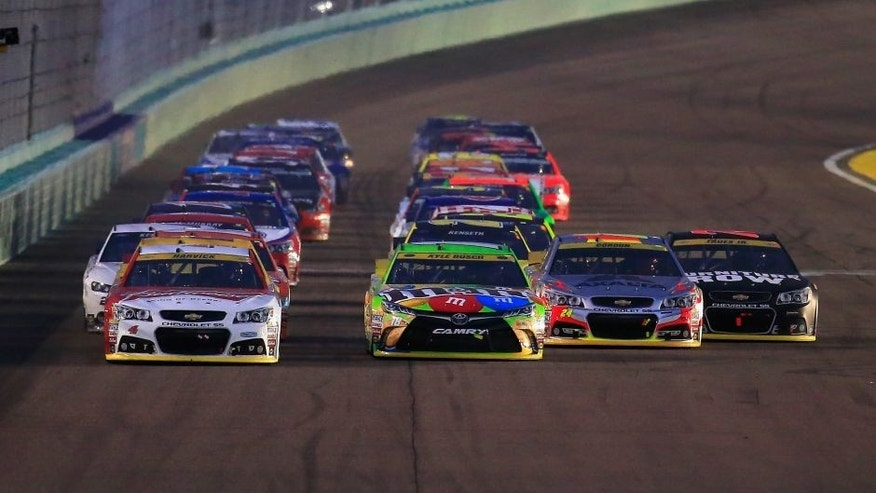 HOMESTEAD, FL - NOVEMBER 22: Kevin Harvick, driver of the #4 Budweiser/Jimmy John's Chevrolet, Kyle Busch, driver of the #18 M&M's Crispy Toyota, Jeff Gordon, driver of the #24 AXALTA Chevrolet, and Martin Truex Jr., driver of the #78 Furniture Row/Denver Mattress Chevrolet, lead the field during a restart during the NASCAR Sprint Cup Series Ford EcoBoost 400 at Homestead-Miami Speedway on November 22, 2015 in Homestead, Florida. (Photo by Chris Trotman/NASCAR via Getty Images)