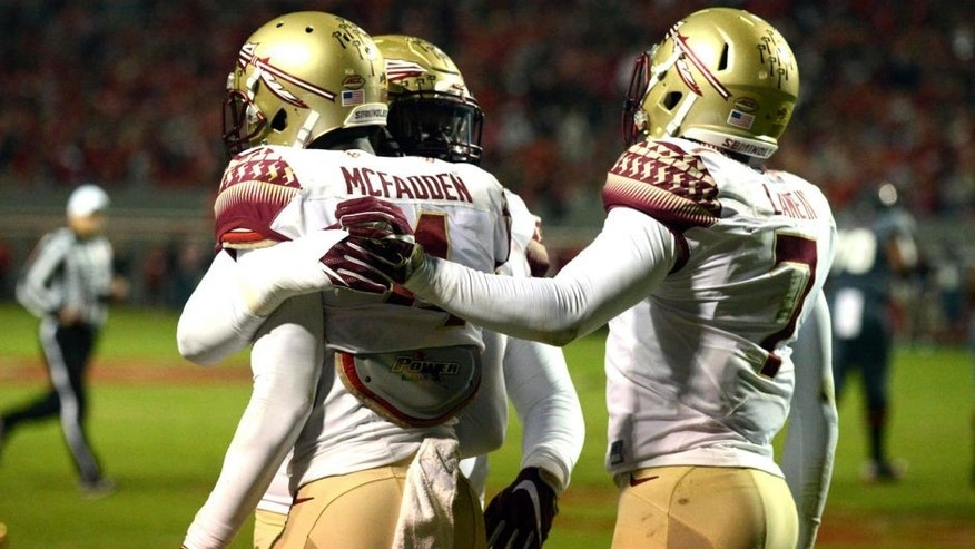 Nov 5, 2016; Raleigh, NC, USA; Florida State Seminoles defensive back Tarvarus McFadden (4) is congratulated by teammates after an interception during the first half against the North Carolina State Wolfpack at Carter Finley Stadium. Mandatory Credit: Rob Kinnan-USA TODAY Sports