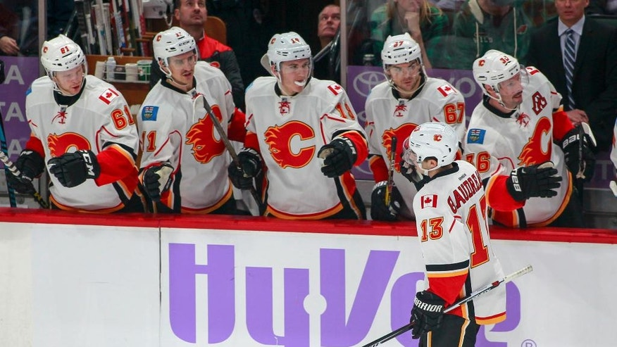 Calgary Flames left wing Johnny Gaudreau (13) is congratulated by teammates after he scored on a power play against the Minnesota Wild during the first period of an NHL hockey game, Tuesday, Nov. 15, 2016, in St. Paul, Minn. (AP Photo/Paul Battaglia)