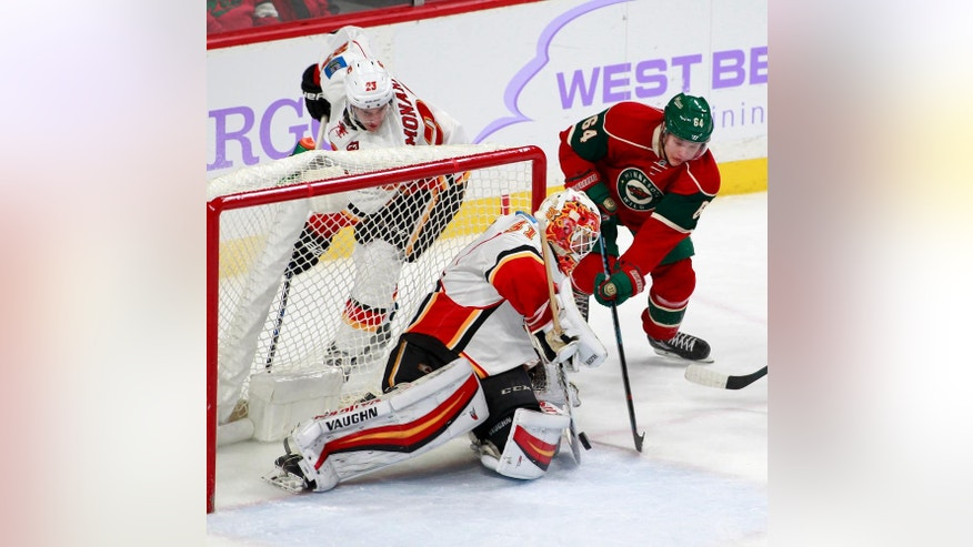 Minnesota Wild center Mikael Granlund (64), of Finland, tries to shoot the puck past Calgary Flames goalie Chad Johnson (31) as Calgary center Sean Monahan (23) watches during the third period of an NHL hockey game, Tuesday, Nov. 15, 2016, in St. Paul, Minn. Calgary won 1-0. (AP Photo/Paul Battaglia)