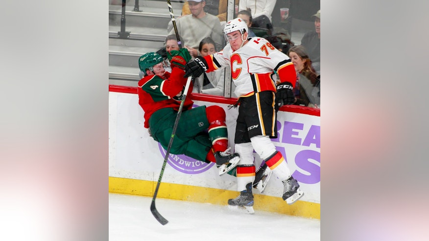 Minnesota Wild defenseman Mike Reilly (4) is checked off the ice by Calgary Flames left wing Micheal Ferland (79) during the first period of an NHL hockey game, Tuesday, Nov. 15, 2016, in St. Paul, Minn. (AP Photo/Paul Battaglia)