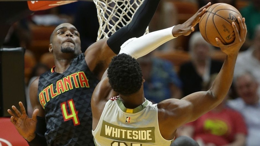 Miami Heat center Hassan Whiteside (21) goes to the basket as Atlanta Hawks forward Paul Millsap (4) defends during the first half of an NBA basketball game, Tuesday, Nov. 15, 2016, in Miami. (AP Photo/Lynne Sladky)