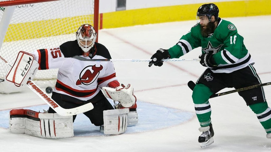 New Jersey Devils goalie Cory Schneider (35) defends Dallas Stars right wing Patrick Eaves (18) during the third period of an NHL hockey game Tuesday, Nov. 15, 2016, in Dallas. The Devils won 2-1 in overtime. (AP Photo/LM Otero)