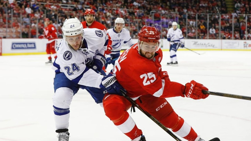 Tampa Bay Lightning right wing Ryan Callahan (24) and Detroit Red Wings defenseman Mike Green (25) battle for the puck in the first period of an NHL hockey game Tuesday, Nov. 15, 2016 in Detroit. (AP Photo/Paul Sancya)