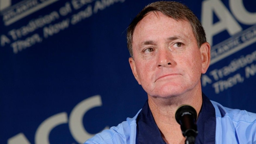 FILE - In this July 25, 2011 file photo, North Carolina coach Butch Davis pauses during interviews at the Atlantic Coast Conference Football Kickoff in Pinehurst, N.C. Davis was hired Monday, Nov. 14, 2016, as the new coach at FIU. (AP Photo/Gerry Broome, File)