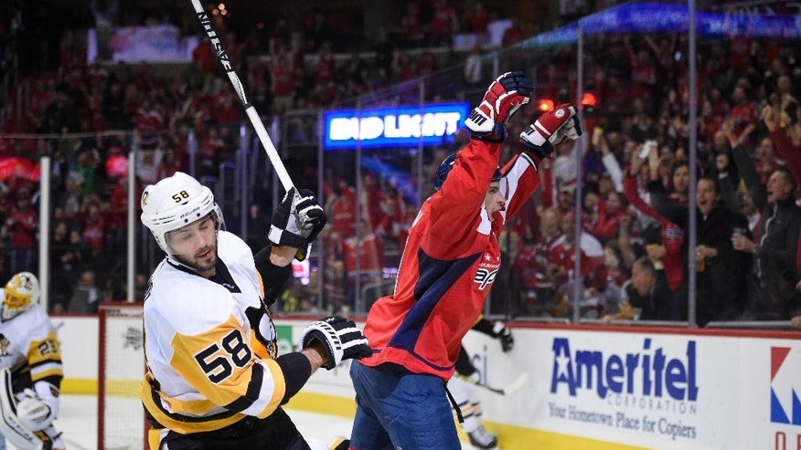 Washington Capitals defenseman Dmitry Orlov, of Russia, right, celebrates his goal during the second period of an NHL hockey game as Pittsburgh Penguins defenseman Kris Letang (58) skates by, Wednesday, Nov. 16, 2016, in Washington. (AP Photo/Nick Wass)
