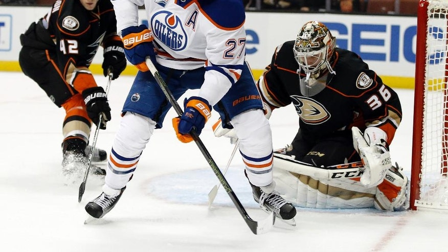 Edmonton Oilers left wing Milan Lucic (27) controls the puck in front of Anaheim Ducks goalie John Gibson (36) and defenseman Josh Manson (42) during the first period of an NHL hockey game in Anaheim, Calif., Tuesday, Nov. 15, 2016. (AP Photo/Alex Gallardo)