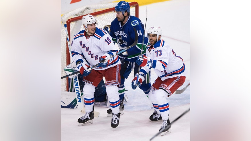 New York Rangers' Brandon Pirri, right, and J.T. Miller, left, celebrate Pirri's goal in front of Vancouver Canucks' Erik Gudbranson during the second period of an NHL hockey game Tuesday, Nov. 15, 2016, in Vancouver, British Columbia. (Darryl Dyck/The Canadian Press via AP)