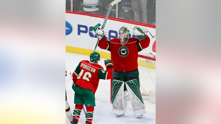 Minnesota Wild goalie Devan Dubnyk (40) celebrates with teammate Minnesota Wild defenseman Jared Spurgeon (46) after they beat the Boston Bruins 1-0 during an NHL hockey game, Thursday, Nov. 17, 2016, in St. Paul, Minn. (AP Photo/Paul Battaglia)