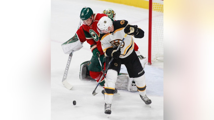 Boston Bruins right wing Jimmy Hayes (11) tries to control the puck as he is defended by Minnesota Wild defenseman Jonas Brodin, of Sweden (25) in front of Minnesota goalie Devan Dubnyk (40) during the first period of an NHL hockey game, Thursday, Nov. 17, 2016, in St. Paul, Minn. Minnesota won 1-0. (AP Photo/Paul Battaglia)