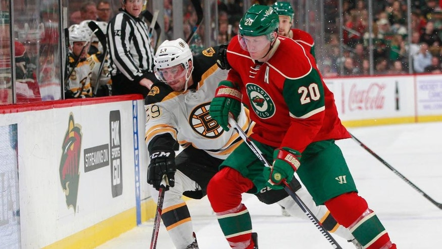 Boston Bruins center Tim Schaller (59) and Minnesota Wild defenseman Ryan Suter (20) battle for the puck during the second period of an NHL hockey game, Thursday, Nov. 17, 2016, in St. Paul, Minn. (AP Photo/Paul Battaglia)