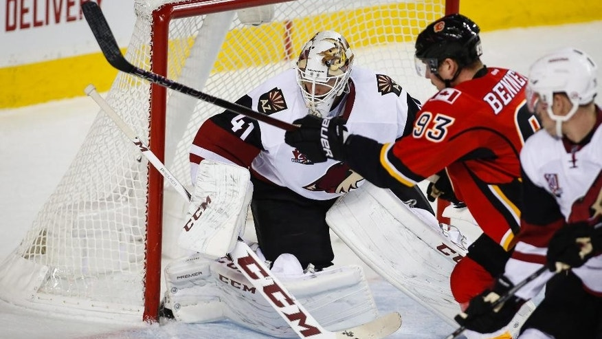 Arizona Coyotes goalie Mike Smith, left, looks on as Calgary Flames' Sam Bennett chases a rebound during first period NHL hockey action in Calgary, Alberta, Wednesday, Nov. 16, 2016. (Jeff McIntosh/The Canadian Press via AP)