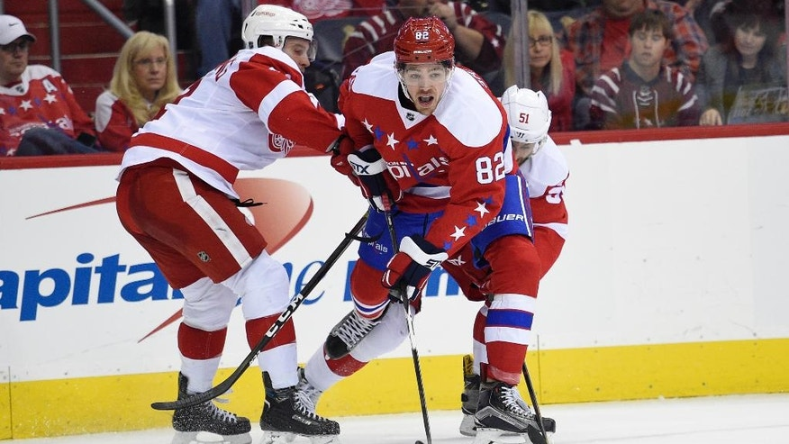 Washington Capitals center Zachary Sanford (82) battles for the puck against Detroit Red Wings center Luke Glendening (41) and center Frans Nielsen (51) during the second period of an NHL hockey game, Friday, Nov. 18, 2016, in Washington. (AP Photo/Nick Wass)