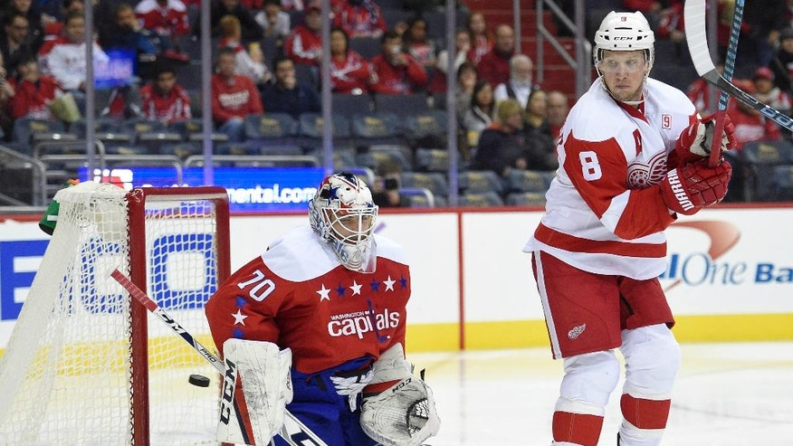 Washington Capitals goalie Braden Holtby (70) watches the puck fly by wide against Detroit Red Wings left wing Justin Abdelkader (8) during the second period of an NHL hockey game, Friday, Nov. 18, 2016, in Washington. (AP Photo/Nick Wass)