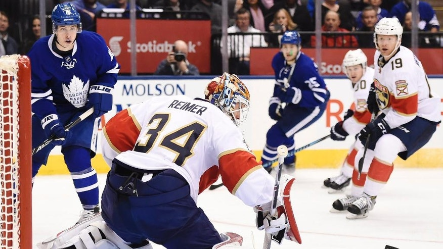 Florida Panthers goalie James Reimer (34) makes a save as Toronto Maple Leafs center Mitchell Marner (16) and Panthers defenseman Michael Matheson (19) look for the rebound during second-period NHL hockey game action in Toronto, Thursday, Nov. 17, 2016. (Nathan Denette/The Canadian Press via AP)