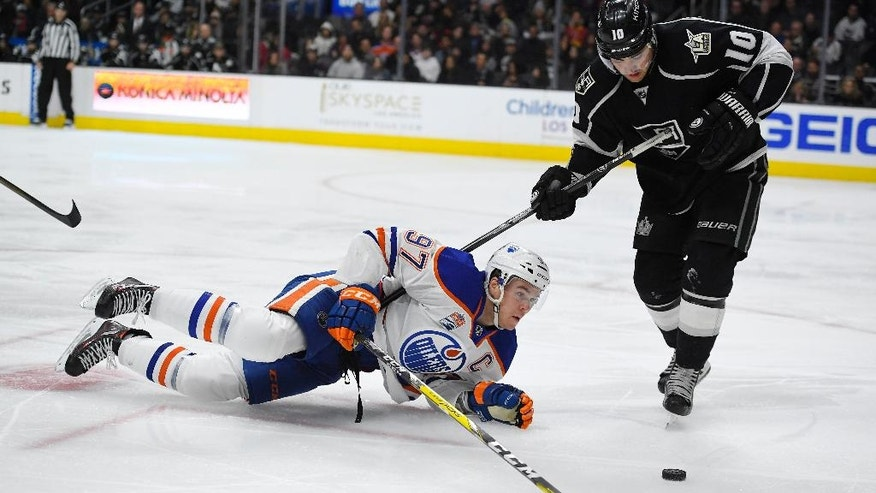 Edmonton Oilers center Connor McDavid, left, falls as he tries to pass the puck while under pressure from Los Angeles Kings right wing Devin Setoguchi during the third period of an NHL hockey game, Thursday, Nov. 17, 2016, in Los Angeles. The Kings won 4-2. (AP Photo/Mark J. Terrill)