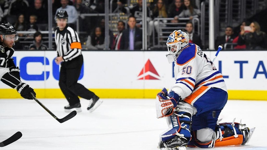 Los Angeles Kings center Jeff Carter, left, scores a sort-handed goal on Edmonton Oilers goalie Jonas Gustavsson, of Sweden, during the second period of an NHL hockey game, Thursday, Nov. 17, 2016, in Los Angeles. (AP Photo/Mark J. Terrill)