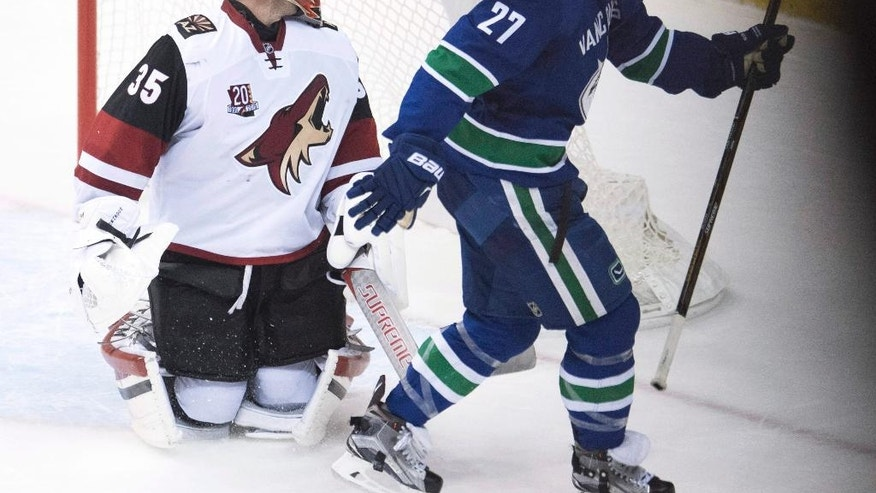 Vancouver Canucks defenseman Ben Hutton (27) celebrates his game-winning goal past Arizona Coyotes goalie Louis Domingue (35) in overtime of an NHL hockey game Thursday, Nov. 17, 2016, in Vancouver, British Columbia. Vancouver won 3-2. (Jonathan Hayward/The Canadian Press via AP)