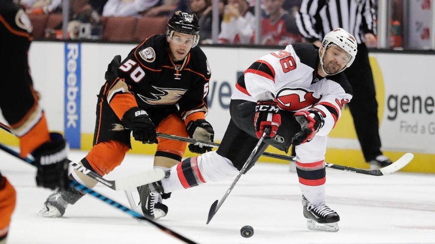 New Jersey Devils' Vernon Fiddler, right, reaches for the puck as he is followed by Anaheim Ducks' Antoine Vermette during the first period of an NHL hockey game Thursday, Nov. 17, 2016, in Anaheim, Calif. (AP Photo/Jae C. Hong)