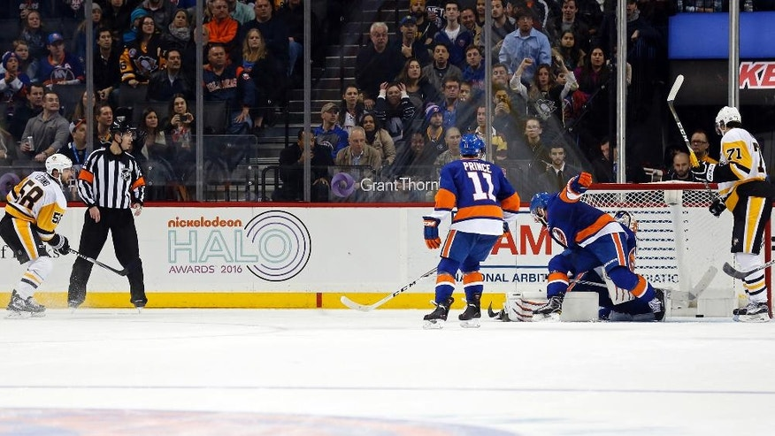 Pittsburgh Penguins defenseman Kris Letang (58) scores during overtime of an NHL hockey game against the New York Islanders, Friday, Nov. 18, 2016, in New York. The Penguins won 3-2. (AP Photo/Adam Hunger)