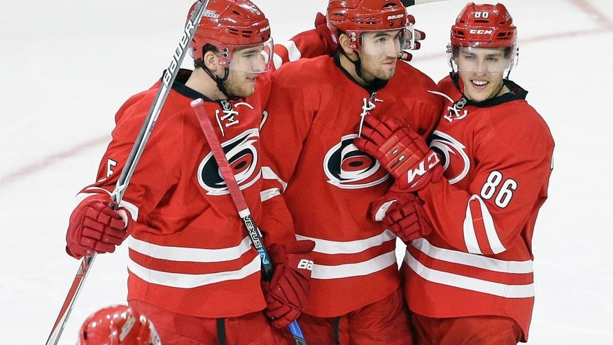 Carolina Hurricanes' Victor Rask, center, of Sweden, is congratulated by Noah Hanifin (5) and Teuvo Teravainen (86) of Finland following Rask's goal against the Montreal Canadiens during the third period of an NHL hockey game in Raleigh, N.C., Friday, Nov. 18, 2016. Carolina won 3-2. (AP Photo/Gerry Broome)