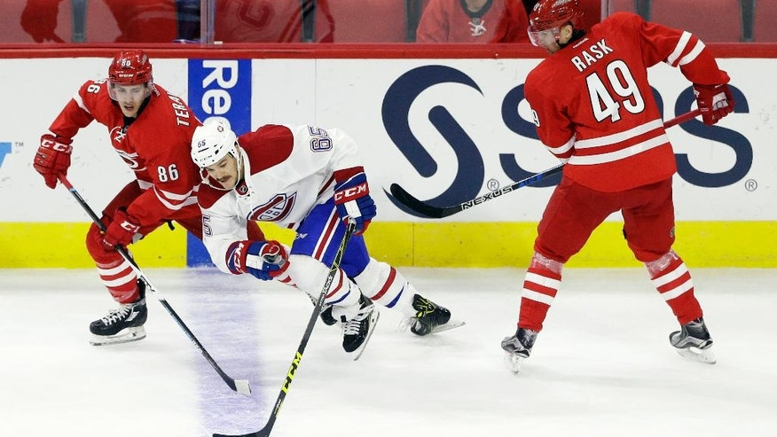 Carolina Hurricanes' Teuvo Teravainen (86), of Finland, and Hurricanes' Victor Rask (49), of Sweden, chase the puck with Montreal Canadiens' Andrew Shaw (65) during the third period of an NHL hockey game in Raleigh, N.C., Friday, Nov. 18, 2016. Carolina won 3-2. (AP Photo/Gerry Broome)