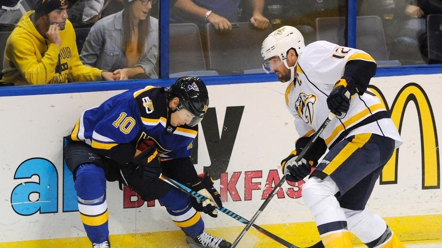 St. Louis Blues' Scottie Upshall (10) and Nashville Predators' Mike Fisher (12) battle for the puck during the first period of an NHL hockey game, Saturday, Nov. 19, 2016, in St. Louis. (AP Photo/Bill Boyce)