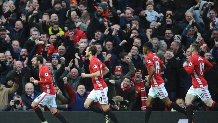 Manchester United's Juan Mata, left, leads celebrations after scoring against Arsenal during the English Premier League soccer match between Manchester United and Arsenal at Old Trafford in Manchester, England, Saturday, Nov. 19, 2016. (AP Photo/Rui Vieira)