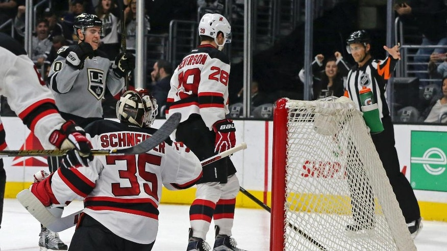 New Jersey Devils goalie Cory Schneider (35) reacts after a goal by Los Angeles Kings left winger Tanner Pearson (70), left rear, in the second period of an NHL hockey game in Los Angeles Saturday, Nov. 19, 2016. (AP Photo/Reed Saxon)