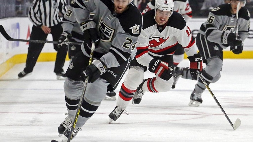 Los Angeles Kings defenseman Derek Forbort (24) and New Jersey Devils right winger P.A. Parenteau (11) battle in the first period of an NHL hockey game in Los Angeles Saturday, Nov. 19, 2016. (AP Photo/Reed Saxon)