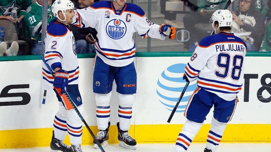 Edmonton Oilers' Andrej Sekera (2) of Slovakia and Jesse Puljujarvi (98) of Sweden celebrate with Connor McDavid after McDavid scored in the third period of an NHL hockey game against the Dallas Stars on Saturday, Nov. 19, 2016, in Dallas. The score was McDavid's third of the game. (AP Photo/Tony Gutierrez)