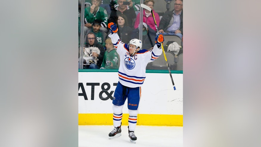 Edmonton Oilers center Connor McDavid (97) celebrates scoring against the Dallas Stars in the third period of an NHL hockey game, Saturday, Nov. 19, 2016, in Dallas. The score was McDavid's third of the game. (AP Photo/Tony Gutierrez)