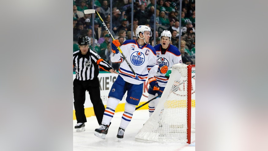 Edmonton Oilers center Connor McDavid (97) and Jesse Puljujarvi (98) of Sweden celebrate a goal by McDavid in the second period of an NHL hockey game against the Dallas Stars on Saturday, Nov. 19, 2016, in Dallas. The score was McDavid's second of the game. (AP Photo/Tony Gutierrez)