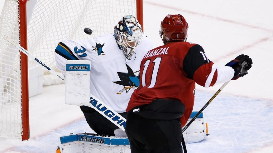 Arizona Coyotes center Martin Hanzal (11) scores the game-winning goal against San Jose Sharks goalie Martin Jones (31) during overtime of an NHL hockey game Saturday, Nov. 19, 2016, in Glendale, Ariz. The Coyotes defeated the Sharks 3-2. (AP Photo/Ross D. Franklin)