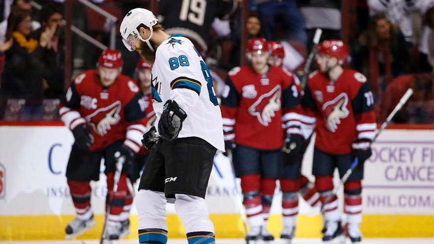 As Arizona Coyotes celebrate a goal in the background, San Jose Sharks defenseman Brent Burns (88) skates with his head down during the first period of an NHL hockey game Saturday, Nov. 19, 2016, in Glendale, Ariz. (AP Photo/Ross D. Franklin)