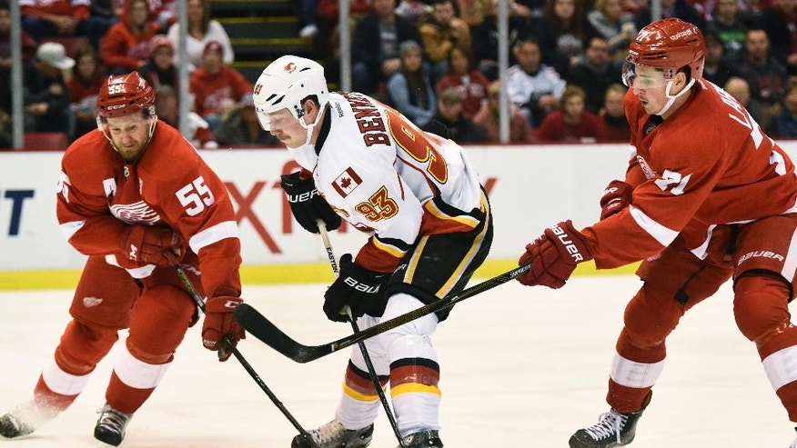 Calgary Flames center Sam Bennett (93) has the puck knocked away by Detroit Red Wings defenseman Niklas Kronwall (55) of Sweden and center Dylan Larkin (71) during the first period of an NHL hockey game in Detroit, Sunday, Nov. 20, 2016. (AP Photo/Jose Juarez)