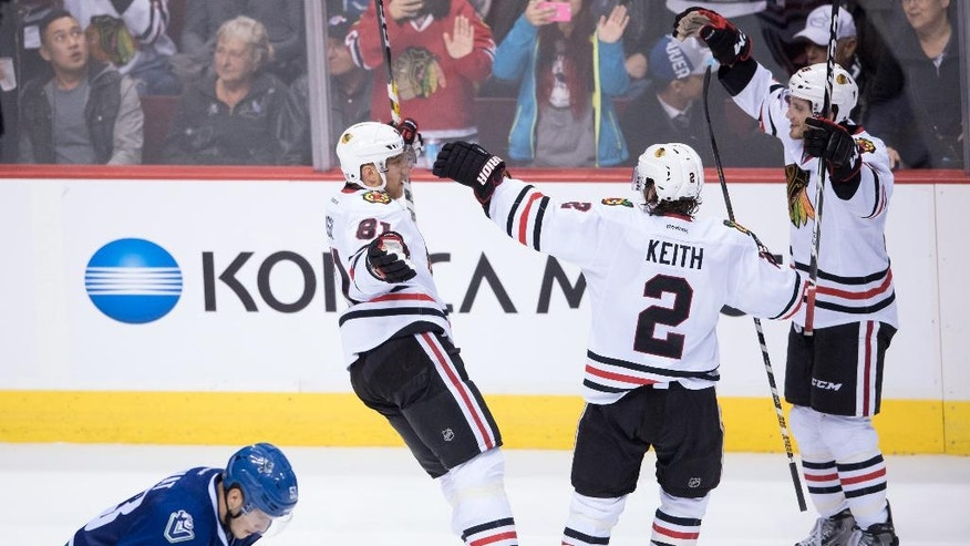Chicago Blackhawks' Marian Hossa, of Slovakia, top from left to right, Duncan Keith and Ryan Hartman celebrate Hossa's winning goal in front of Vancouver Canucks' Bo Horvat, bottom left, during the overtime period of an NHL hockey game in Vancouver, British Columbia, on Saturday Nov. 19, 2016. (Darryl Dyck/The Canadian Press via AP)